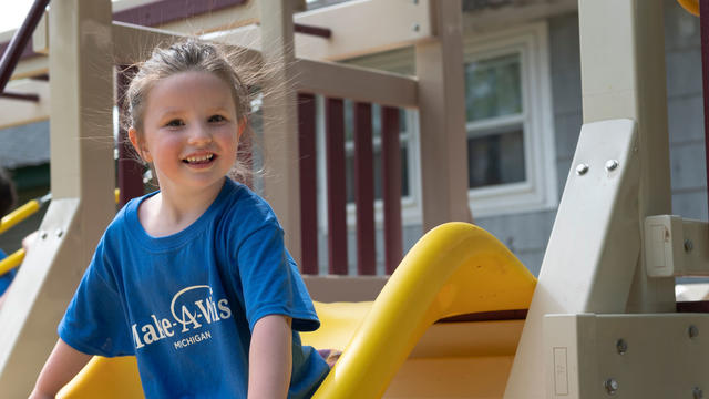 A young child in a royal blue Make-A-Wish t-shirt and multicolored plaid skirt sits at the top of a yellow playground slide with a wide smile.
