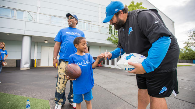 A child in a royal blue Make-A-Wish t-shirt and jean shorts holds a football in one hand and uses the other hand to fistbump an adult in Detroit Lions clothing who is signing a second football.