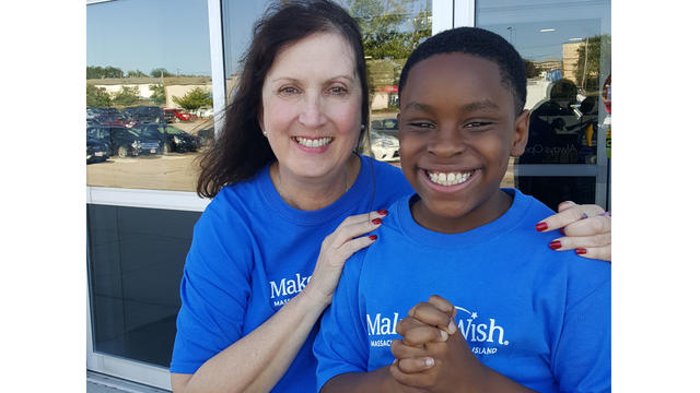 Make-A-Wish volunteer celebrating wish child Kelani's shopping spree wish with him, and both are wearing blue Make-A-Wish t-shirts